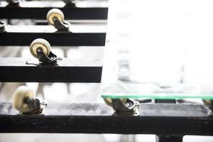 Валики передвигают стекло по станку.