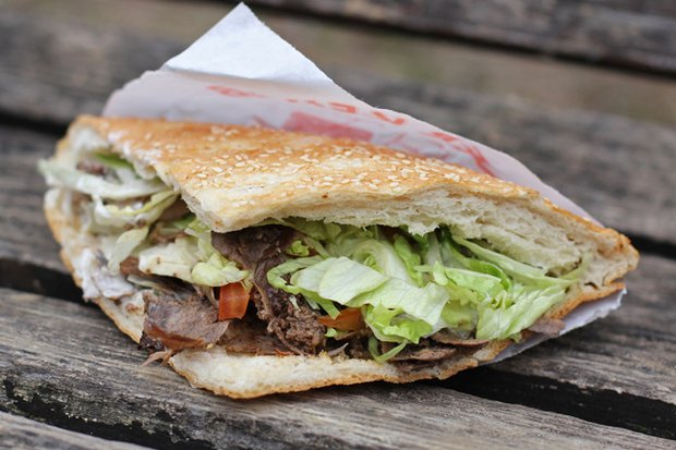 Дёнер -- турецкий фастфуд. Это рубленое мясо с вертела, свежие овощи и соус в лепешке. Фото с сайта andberlin.com