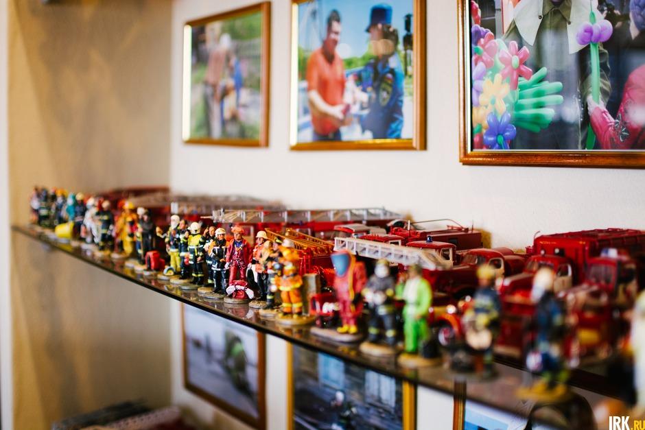 Несколько полок заполнены различными моделями пожарных машин и фигурок пожарных.
