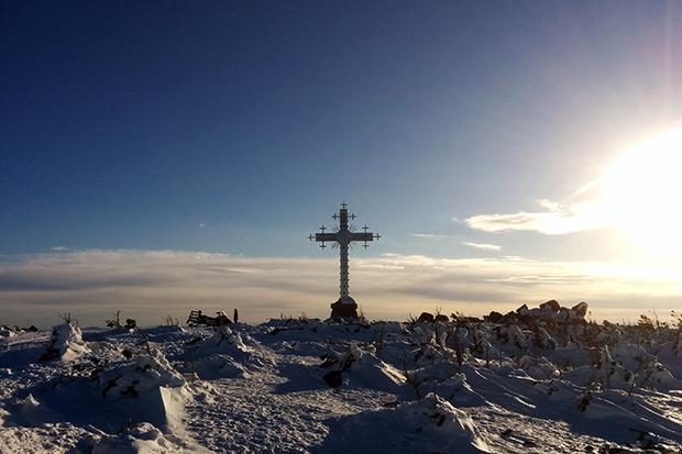 Это поклонный крест на вершине, к которой не ведет ни один подъемник. Вас сюда с радостью доставят на снегоходе за 700 рублей с человека. Потом можно самостоятельно скатиться по дикой трассе