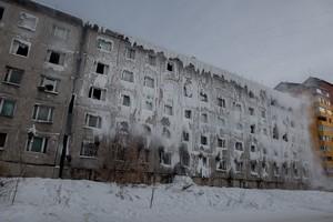 Одна часть здания ветхая, с разбитыми стеклами в оконных проемах, другая похожа на ледяную пещеру