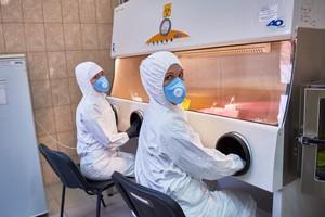 Сотрудники лаборатории работают в защитных костюмах, масках, перчатках, сапогах или галошах