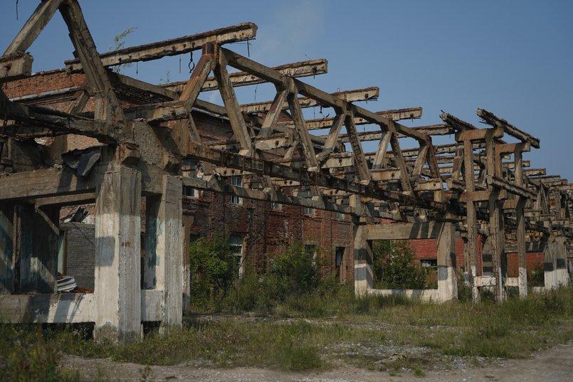 Заброшенные здания, в прошлом — цеха, выбитые стекла, разбросанная арматура, открытые люки, трубы – так выглядит сегодня территория «Усольехимпрома»
