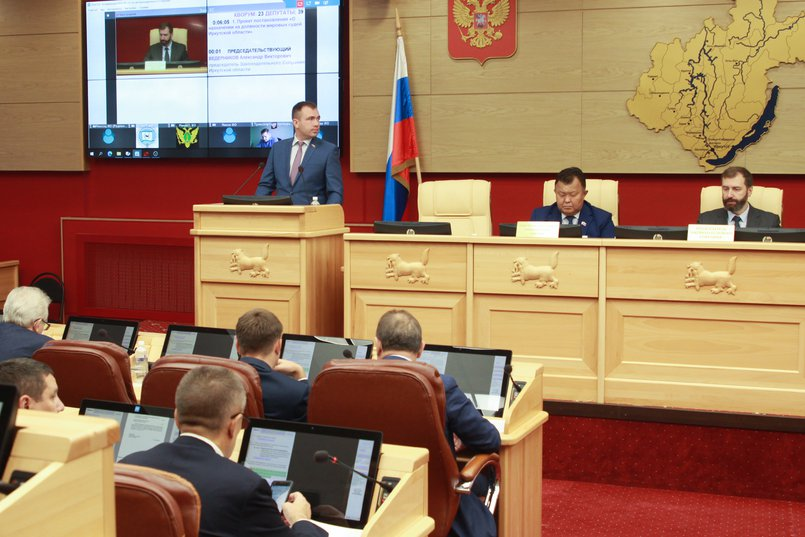 У трибуны Виталий Перетолчин, председатель комитета по законодательству о государственном строительстве области и местном самоуправлении