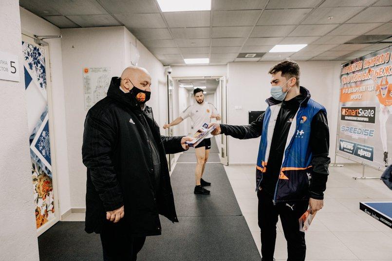 Артем передает программки представителю хоккейного клуба «СКА-Нефтяник»