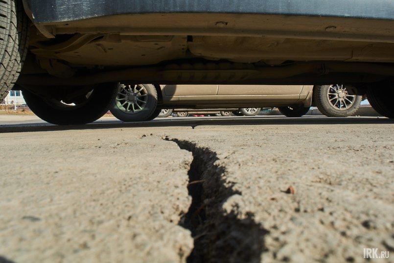Вблизи склона со стороны залива на тротуарах и асфальте парковочного кармана образовались трещины и разломы
