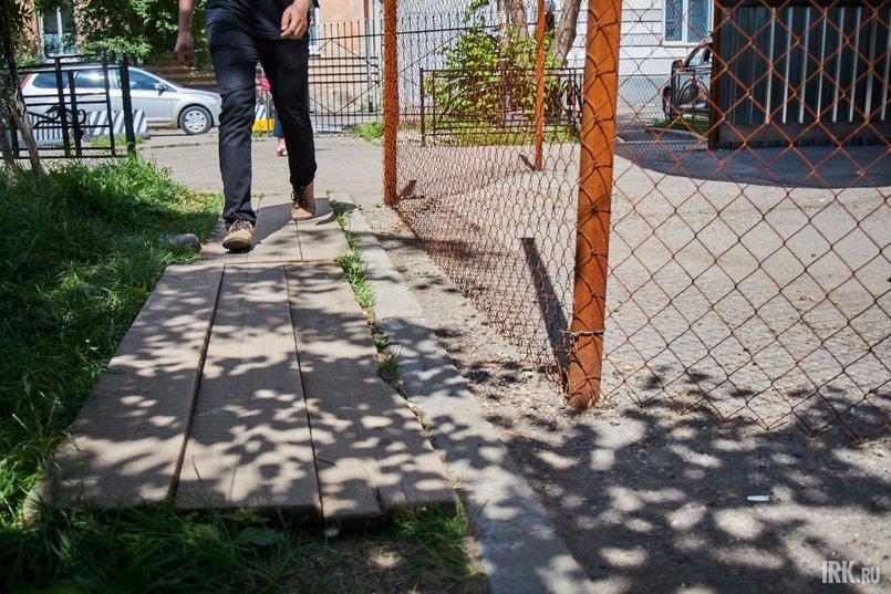 Со стороны Литвинова установили ограждения от летящей штукатурки и бетона. Железные столбы поставили прямо на тротуаре, а для пешеходов на газоне положили деревянные доски